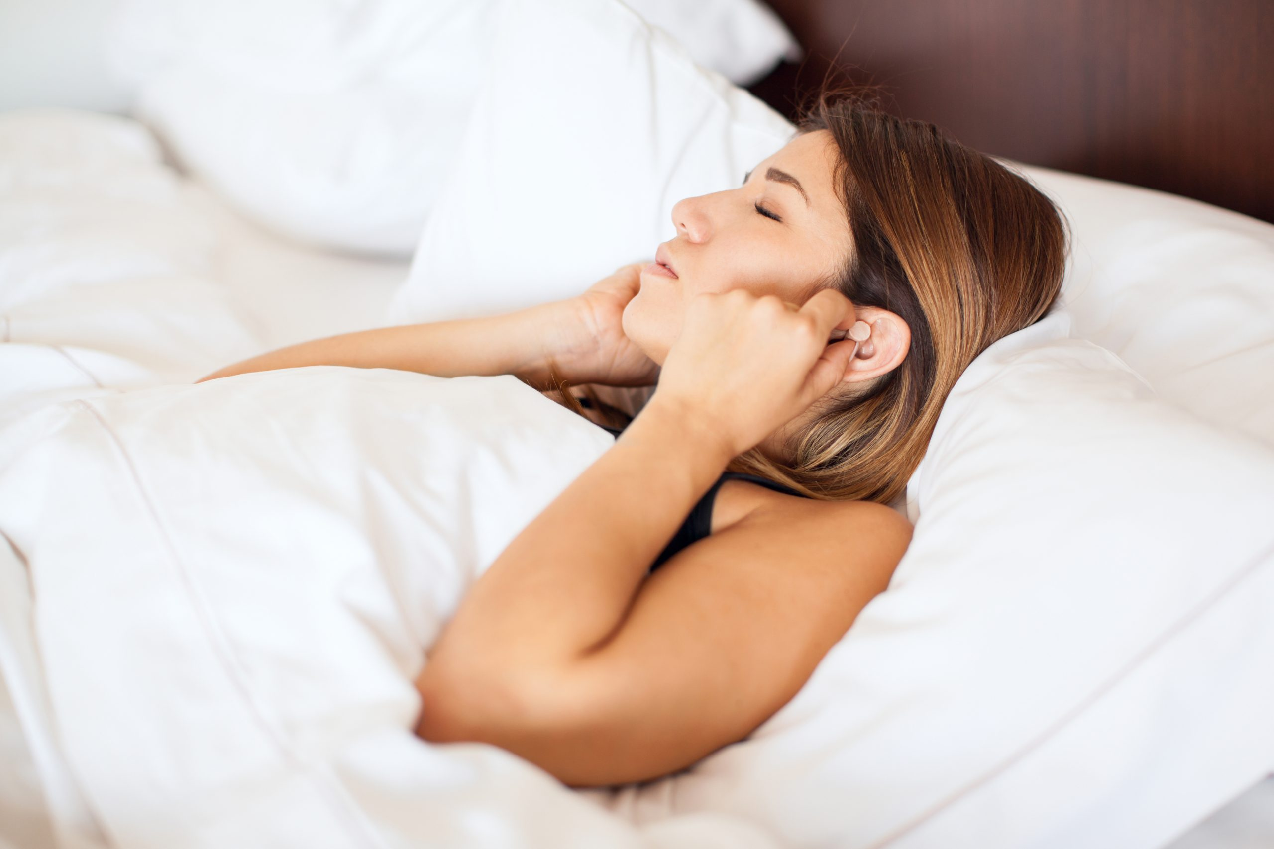 Profile view of a cute young woman putting some earplugs on before going to sleep in a hotel bed
